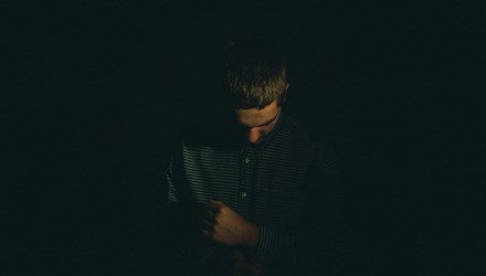 Man head down in darkness -Jordan Whitfield 97343 Unsplash 1